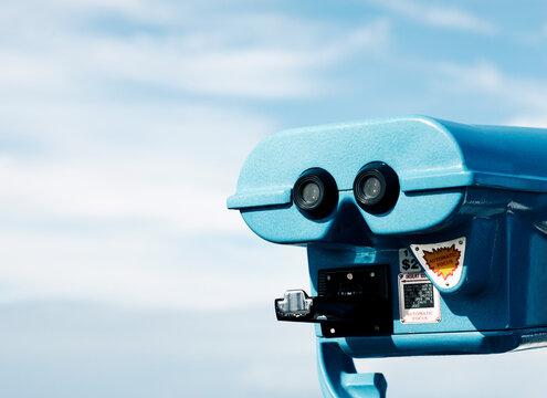 Blue lookout binoculars against blue cloudy sky