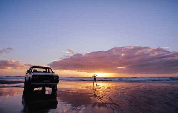 White Ute parked on the beach and lone person standing by the water at sunset