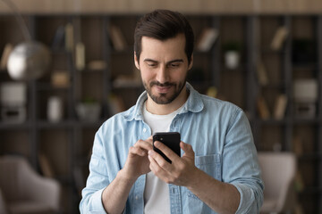 Fototapeta Close up satisfied man using phone, looking at screen, standing at home, positive young male holding smartphone, chatting in social network with friends or shopping online, enjoying leisure time obraz