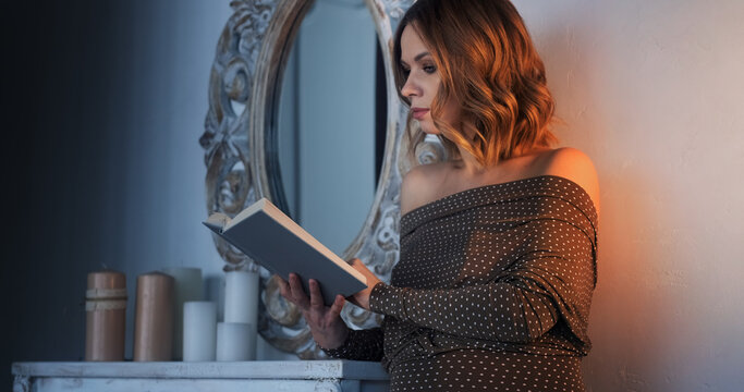 Woman stands by the retro mirror and reads a book