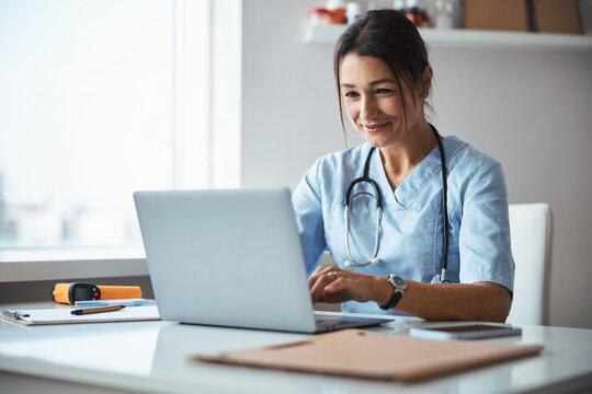 Joyful female doctor using notebook in clinic