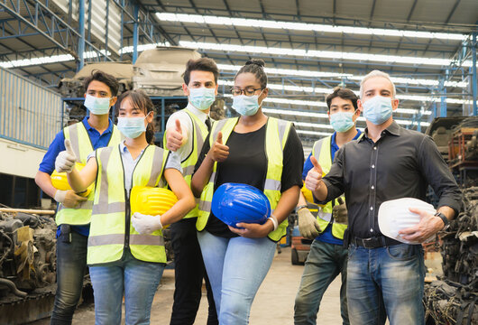 Men and woman work together, show teamwork by giving thumbs up and wear facemask. Caucasian engineer men, black woman, Asian men, Asian woman wear facemask and give thumbs up in factory-warehouse