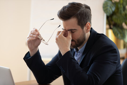 Stressed unhappy overwhelmed young male ceo executive manager workaholic businessman taking off eyeglasses, feeling tired of long computer work, suffering from dry eyes syndrome or strong pain.