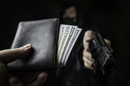 Man's hand holds out wallet of money to robber with gun. Hundred and fifty dollars in open purse. Armed robbery. Firearm is pointed at camera. Criminal in hood and mask. Assault on unarmed man.