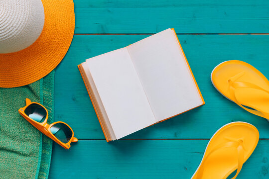 Reading on summer vacation holiday, book with blank mock up pages, flat lay top view