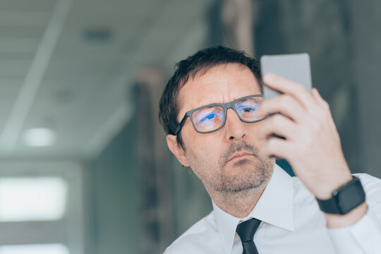 Businessman looking at mobile phone in the office