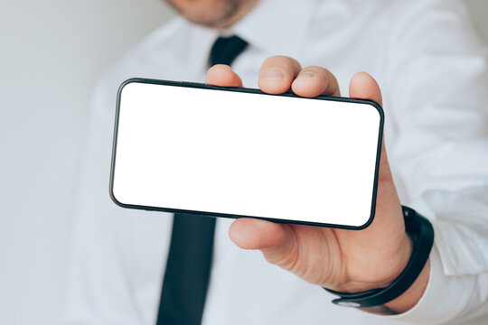Mobile smart phone blank screen mock up in hand of a businessman