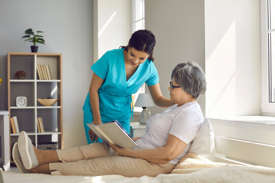 Female home care nurse assists old woman with daily needs. Caregiver for elderly patients talking to relaxed senior lady who's sitting on comfortable bed at home, reading book and enjoying free time