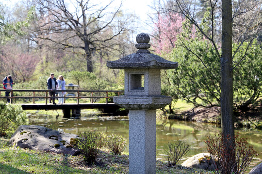 Japanese garden at spring. Old Tachi-gata stone lantern, pond and bridge with tourists surrounded by trees