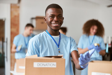 Fototapeta Close up shot of african american young male volunteer in blue uniform, protective gloves smiling and holding cardboard box for Donation