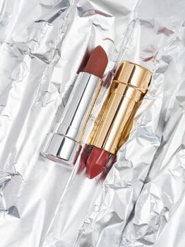 Red nude lipstick in golden and silver tube on metallic background