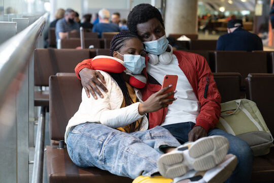 Tired couple of tourists in face masks in airport wait for flight delayed or cancelled due to covid-19 lockdown. African travelers check airplane tickets online with smartphone in boarding lounge hall