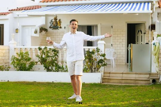A man in white meets his guests against the backdrop of his large house. Purchase of real estate, travel, rent. Guy drinks wine on the lawn