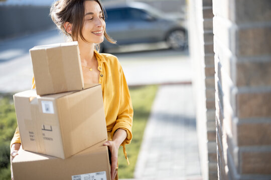 Young happy woman carries home a parcels with goods purchased online, knocking on the door. Concept of online shopping and delivery.