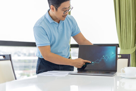 Businessman pointing strategy graph chart on laptop in the office.