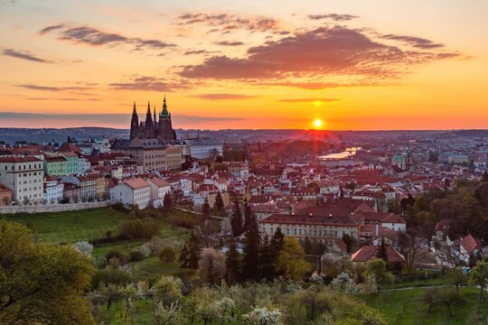 Prague, Czech Republic - May 3 2021: Colorful sunrise view of the city from Petrin hill with the castle, garden, trees, river and buildings. Clouds on the yellow, orange, pink and blue sky.