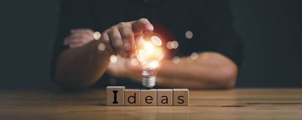 Obraz hand touching on light bulb on wood block with Word Ideas, new idea concept with innovation and inspiration, innovative technology in science and communication concept. - fototapety do salonu