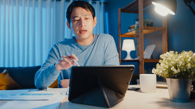 Asia businessman focus online video call meeting assignment on paperwork with colleague in tablet computer in living room at home overtime at night, Work from home coronavirus pandemic concept.