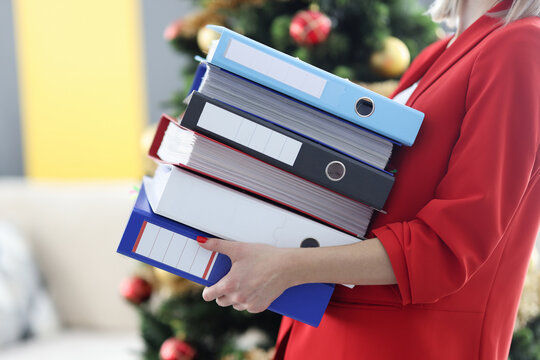 Woman is holding heavy stack of folders with documents.