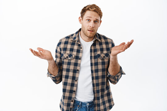 I dont know, whats your problem. Clueless redhead man with strong arms and fit body, shrugging shoulders questioned, cant understand, standing confused against white background