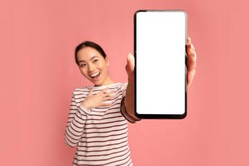 Fototapeta Cool App. Excited Asian Female Demonstrating Smartphone With Big Blank White Screen obraz