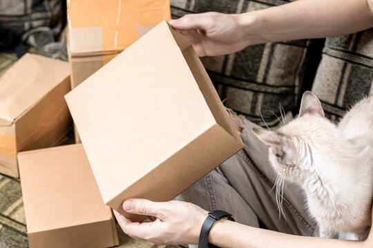 male person indoors unpack cardboard parcel package. men opening box. delivery service concept. online shopping conceptual