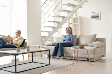 Obraz Older senior family couple spending time at home in modern living room. Middle aged husband reading book relaxing sitting on couch while mature wife using laptop enjoying casual daily activities. - fototapety do salonu