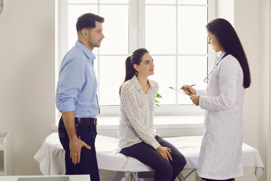 Young married couple in a hospital consults with an experienced doctor on planning a pregnancy. Expectant parents listen to the advice of a female gynecologist. Concept of health and pregnancy.