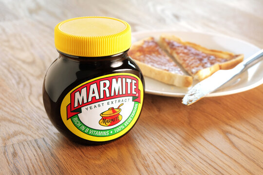 Leeds, United Kingdom - April 22nd, 2015: Jar of Marmite, unopened on wooden table top. Slice of toast on a white plate in background. Marmite is a food paste, made from yeast extract.