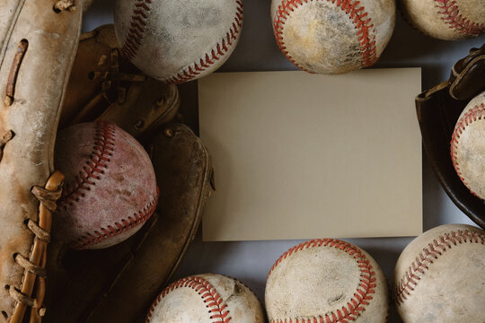 old used baseball balls and glove with copy space on card in background.
