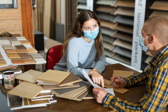 Experienced salesperson in protective face mask working with client offering laminate flooring in shop of building materials