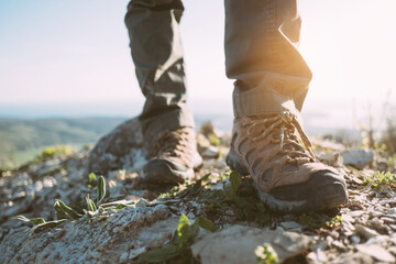 View of the feet of a traveler in trekking boots on the top of the mountain.