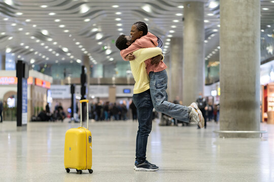 Happy meeting of loving couple after long time. African man and woman excited hugging in airport terminal after separation due to covid-19 lockdown and quarantine. Lovers reunion at airlines reopening