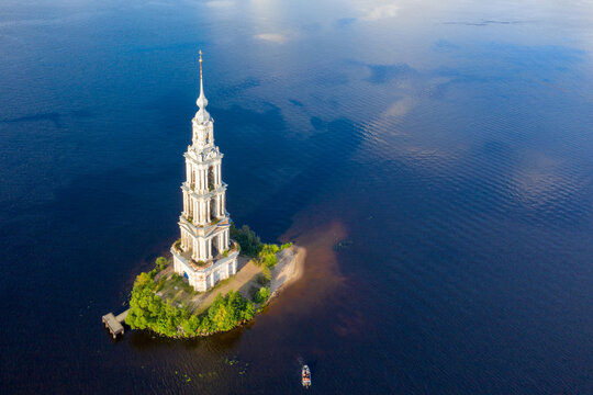 Aerial view of bell tower (1800) of Nikolsky cathedral in the middle of Volga river on sunny summer day. Kalyazin, Tver Oblast, Russia.