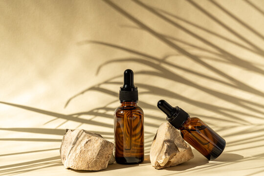 Dark glass cosmetic bottles with a dropper on a beige background with stones and tropical leaves. Natural cosmetics concept, natural essential oil and skin care products