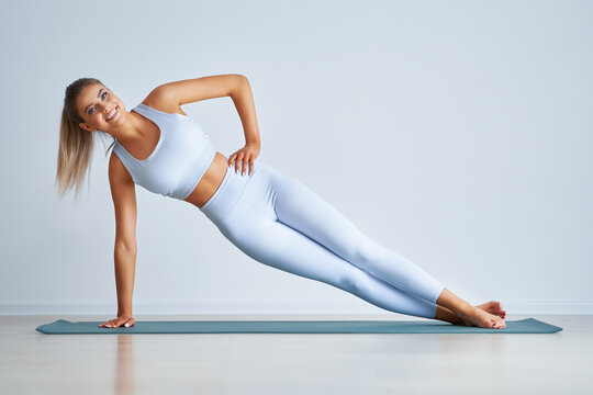 Adult beautiful woman working out over light background