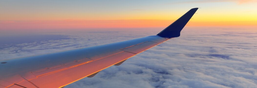 Golden sunset sky with fluffy ornamental cumulus clouds, panoramic view from an airplane, wing close-up. Dreamlike cloudscape. Travel, tourism, vacations, weekend, freedom, peace, hope concepts