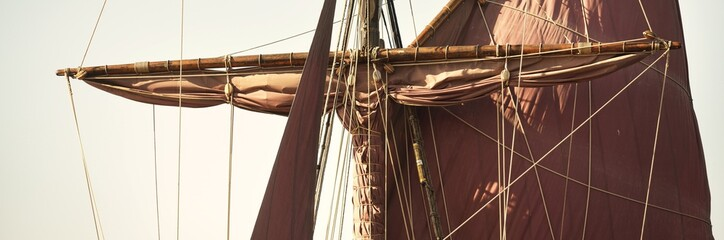 Mast, red sails and rigging of an old classic sailing ship from 18th century, close-up. Clear blue sky