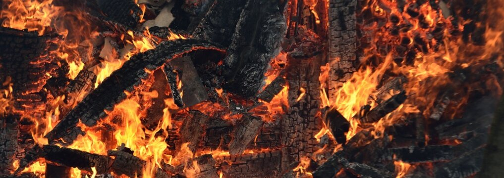 Ruins of the wooden country house and fence in a flame. Fire and smoke textures close-up. Forest fires in summer. Seasons, ecology, ecological issue, environmental damage, disaster, danger concepts