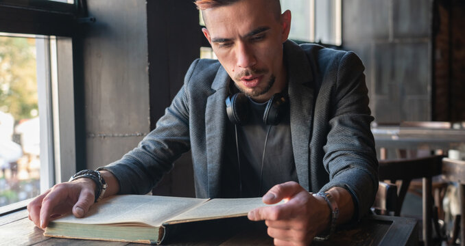 Male student hipster reading a book. Knowledge, education, development concept. Horizontal image.
