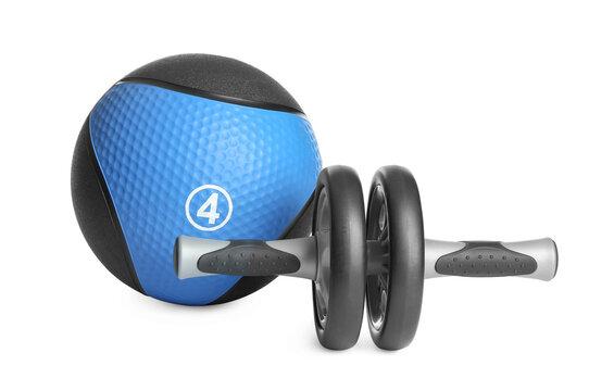 Medicine ball and abdominal wheel on white background