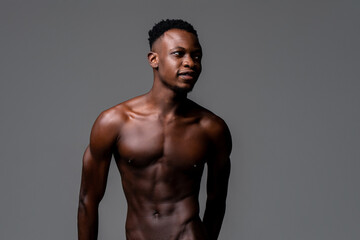 Fototapeta Waist up studio portrait of shirtless young lean fit African man in isolated light gray background obraz