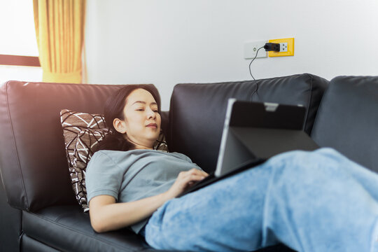 Caucasian woman lying on couch work on laptop.