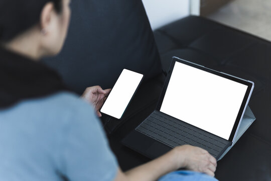 Woman sitting on the couch working online using mobile phone and laptop.