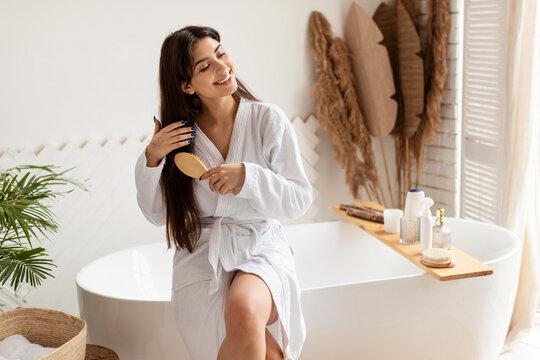 Brunette Female Brushing Hair With Hairbrush Sitting On Bathtub Indoor