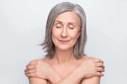 Photo of joyful lovely old woman hug herself closed eyes skin body care isolated on grey color background