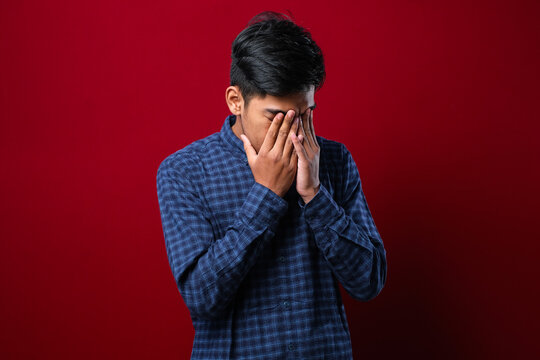 Indian man with mustache wearing casual shirt with sad expression covering face with hands while crying. depression concept