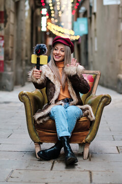 Smiling woman in fur coat vlogging through smart phone while sitting on armchair at alley