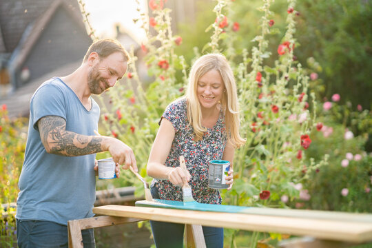 Couple painting wooden plank in garden