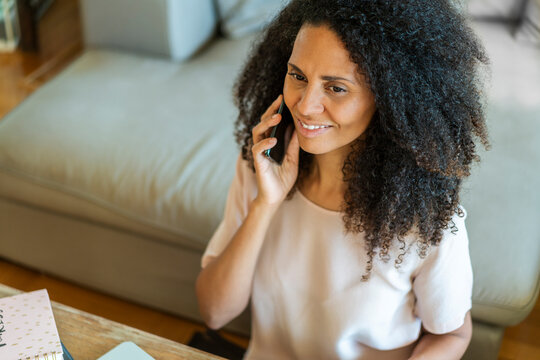 Mid adult businesswoman talking on smart phone while sitting at home